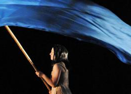 剧院 performance, female carrying a blue flag